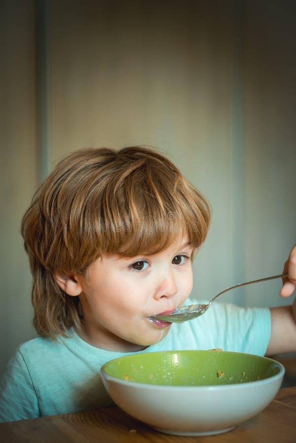 E Τρόφιμα και ποτό για το παιδί Μικρό παιδί που έχει το πρόγευμα στην κουζίνα Συνεδρίαση μικρών παιδιών στον πίνακα και στοκ εικόνα με δικαίωμα ελεύθερης χρήσης