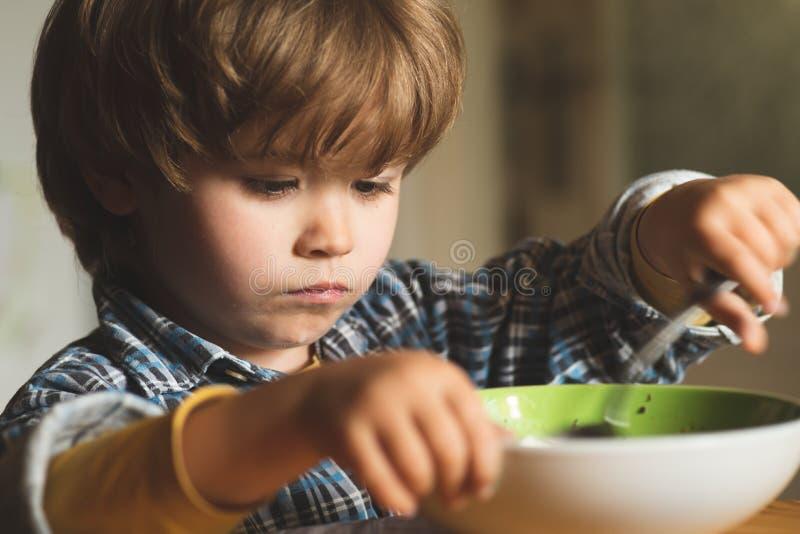 E Τρόφιμα και ποτό για το παιδί Πορτρέτο του γλυκού λίγο γελώντας αγοράκι με την ξανθή τρίχα που τρώει από το πιάτο στοκ φωτογραφίες με δικαίωμα ελεύθερης χρήσης