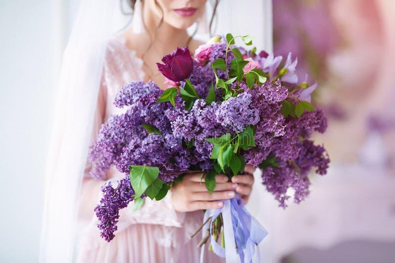 E Όμορφη γυναίκα με τα αισθησιακά χείλια που κρατά τα ιώδη λουλούδια στοκ φωτογραφίες