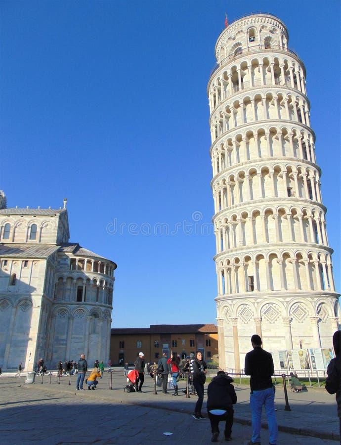 E Башня склонности Пизы с много туристами на заходе солнца стоковые фото