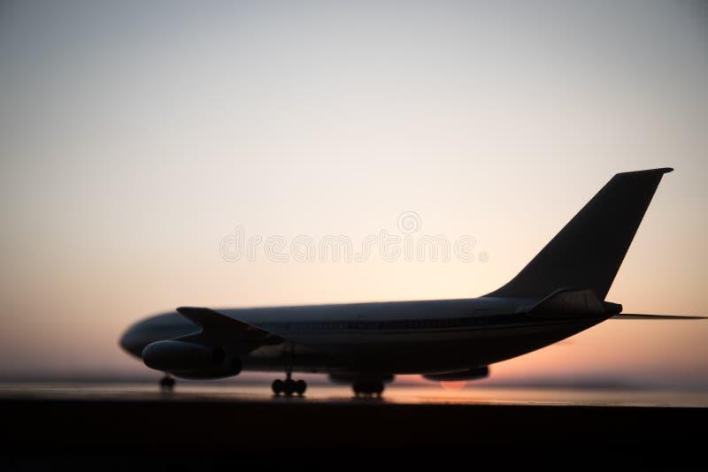 E Белый пассажирский самолет готовый к принимать от взлетно-посадочной дорожки аэропорта Силуэт воздушных судн во время времени з стоковое изображение rf