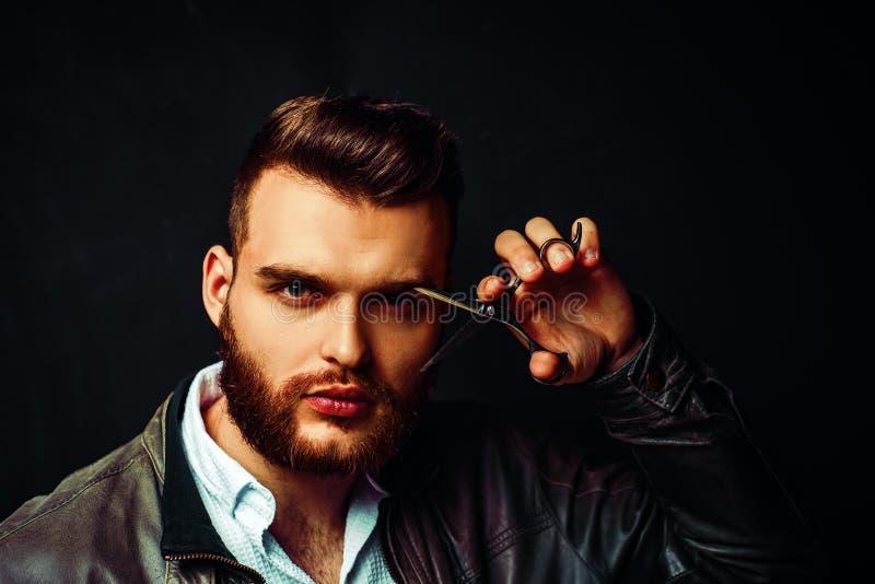 E Бородатый человек, бородатый мужчина Портрет стильного человека с бородой Ножницы парикмахера и прямая бритва стоковые изображения
