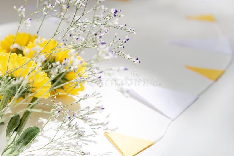 E Букет желтой chrysanthemumHoliday концепции Bouqus лежит на белой таблице окруженной гирляндой флагов стоковая фотография rf
