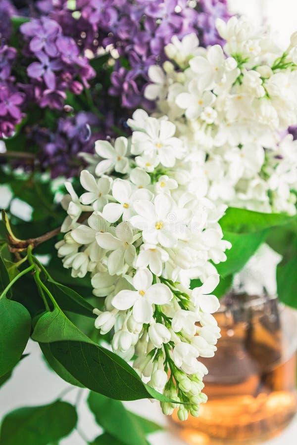 E Букет сирени и белых цветков сирени в стеклянной вазе около положения стоковое изображение