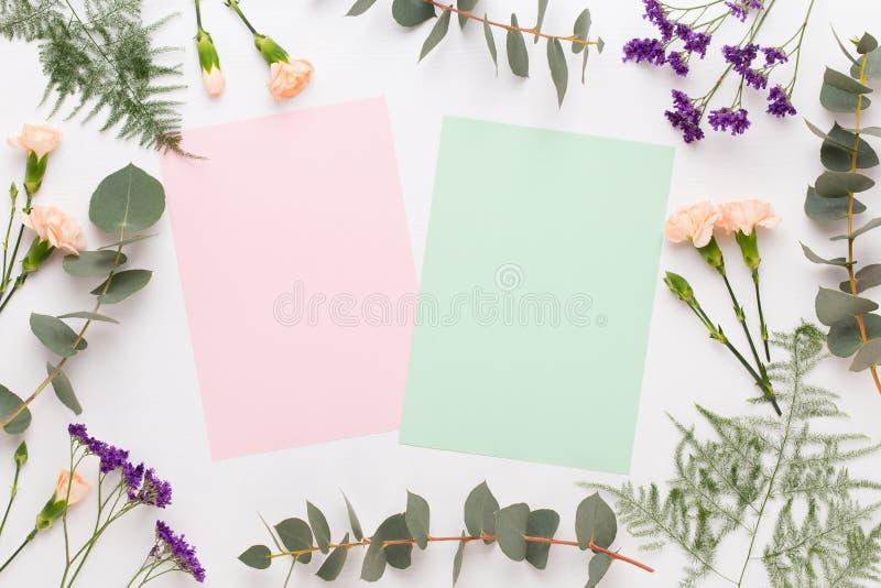 E Бумажный пробел, цветки гвоздики, ветви эвкалипта на пастельной предпосылке Плоское положение, взгляд сверху, spaceFlat экземпл стоковое изображение rf