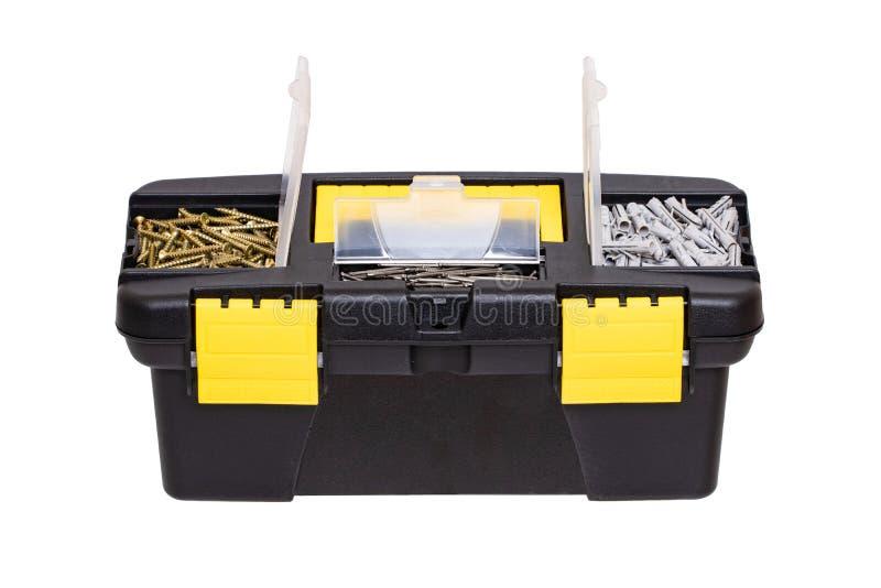 E Крупный план маленькой черной пластиковой коробки инструментального ящика с желтыми ручкой и фермуаром и с ногтями, винтами и ш стоковое изображение rf