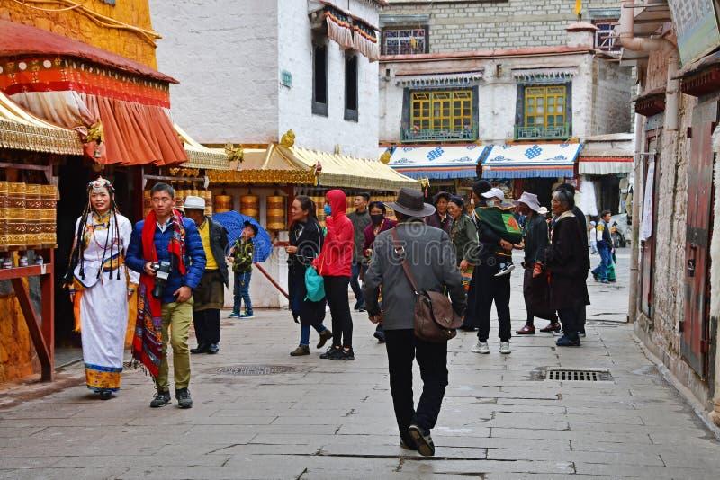E Люди идя около одного из более небольших старых буддийских монастырей в Лхасе на stree Barkhor стоковые изображения rf