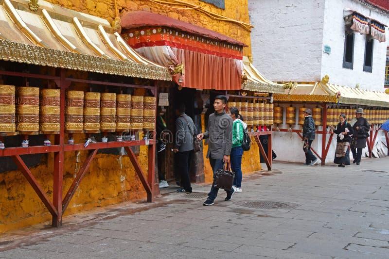 E Люди идя около одного из более небольших старых буддийских монастырей в Лхасе на stree Barkhor стоковое фото