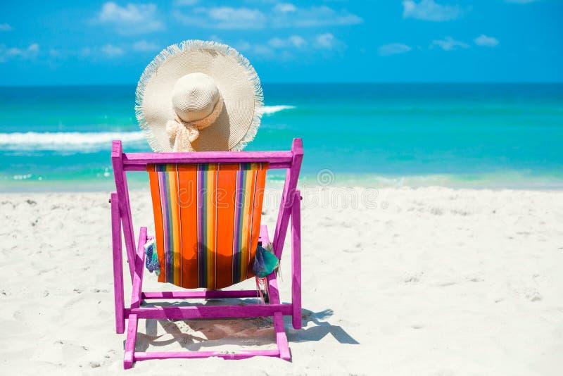 E На пляже, девушка сидит в покрашенных pareo и соломенной шляпе с ее задней частью к камере в шезлонге, релаксации, стоковое фото