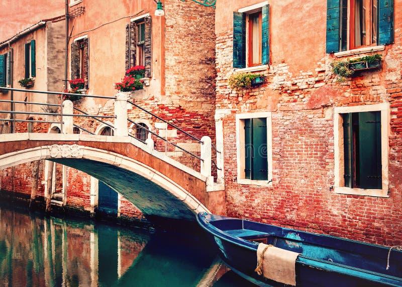 E Небольшой мост над каналом с голубой шлюпкой и традиционными оранжевыми историческими зданиями стоковые изображения