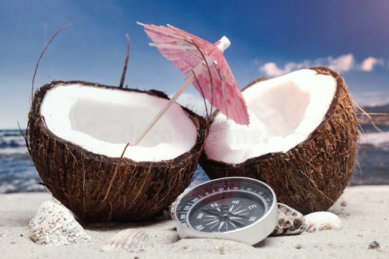 E 2 половины кокоса с зонтиком и компасом на пляже на фоне моря и неба стоковые фотографии rf