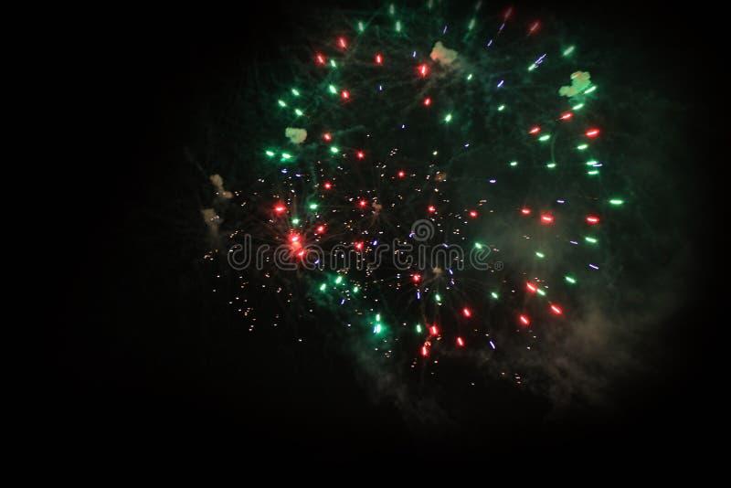 E Салют Тайна предпосылки неба изумляя ярких красных, зеленых и голубых сверкная светов в ночном небе во время нового стоковые изображения