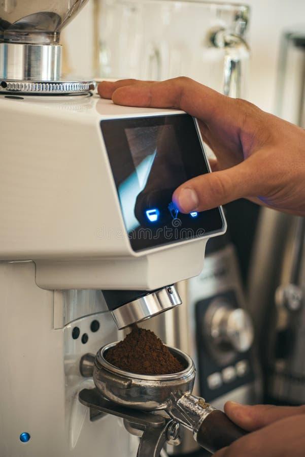 E Свежий земной кофе в portafilter Barista делает эспрессо в кафе r стоковая фотография rf