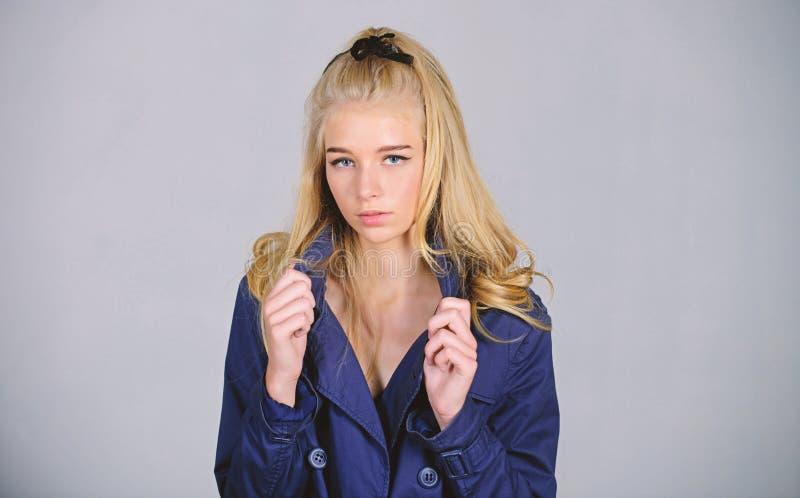 e E Светлые волосы стороны макияжа женщины представляя пальто с воротником r стоковые изображения