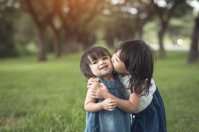 E сестры маленьких девочек целуя и смеясь стоковая фотография