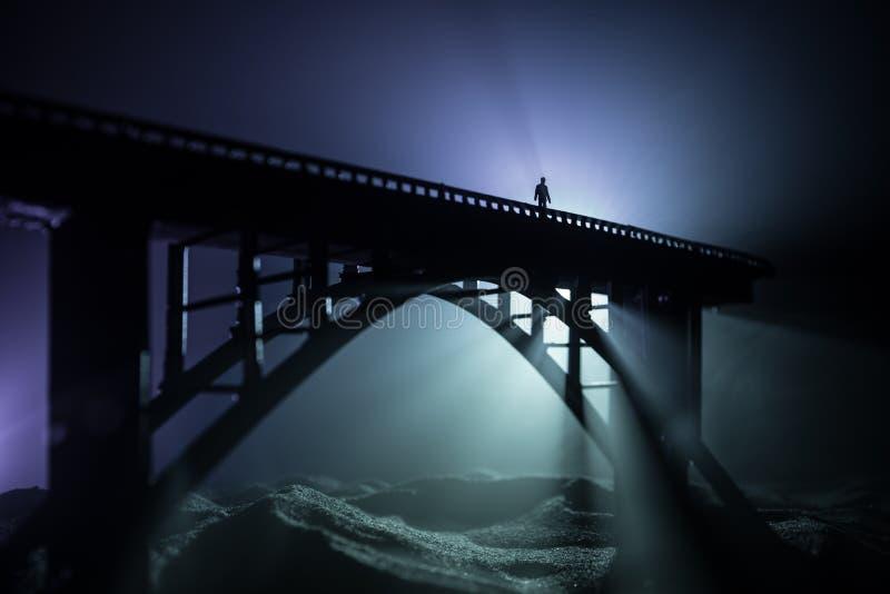 E Силуэт сильного металлического моста вечером с туманным освещает контржурным светом Силуэт положения человека на мосте стоковые фотографии rf