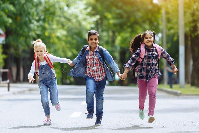 E Смешанная расовая группа в составе счастливые студенты начальной школы с рюкзаками бежать держащ руки outdoors стоковая фотография rf