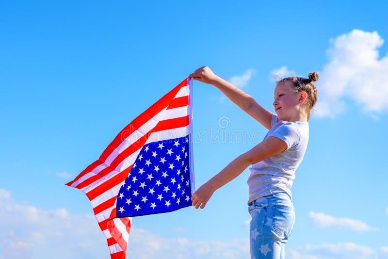 E Счастливый ребенк, милая девушка маленького ребенка с американским флагом США празднуют 4-ое -го июль стоковые изображения rf