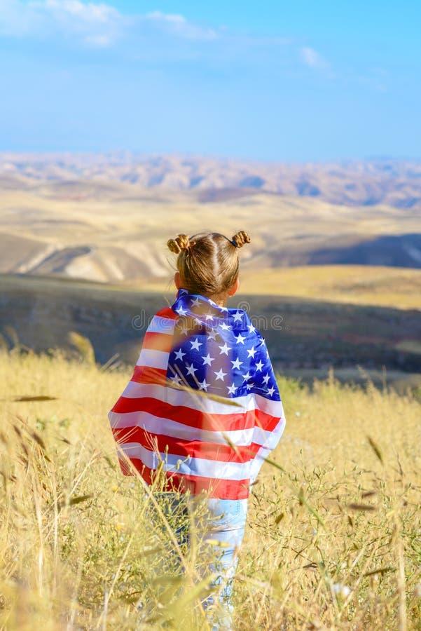 E Счастливый ребенк, милая девушка маленького ребенка с американским флагом США празднуют 4-ое -го июль стоковое фото rf