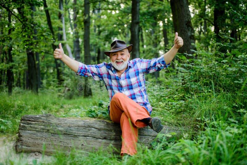 E счастливый forester r пеший туризм в глубокой древесине владелец леса пикник лета или весны старший человек стоковые фото