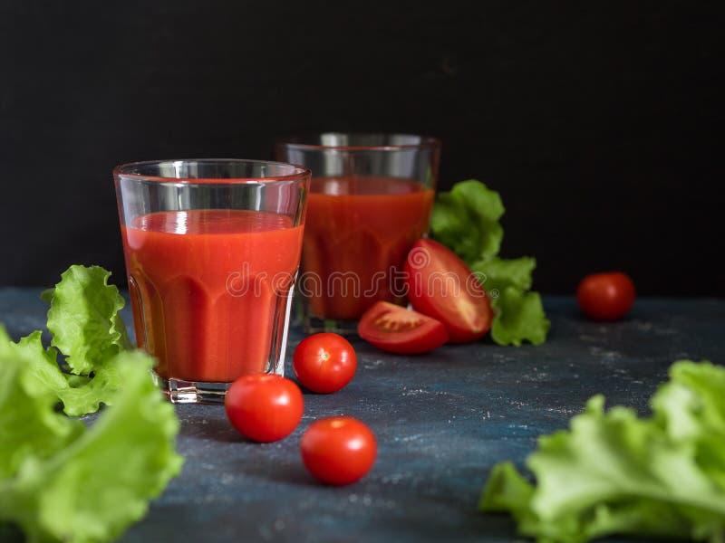 E Традиционный испанский холодный суп гаспачо со зрелыми томатами или свежим соком томата в стеклах на темной предпосылке стоковое фото