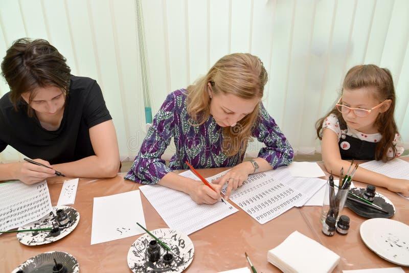 E Учитель показывает сочинительство почерка писем каллиграфического Занятие в студии детей стоковое фото rf