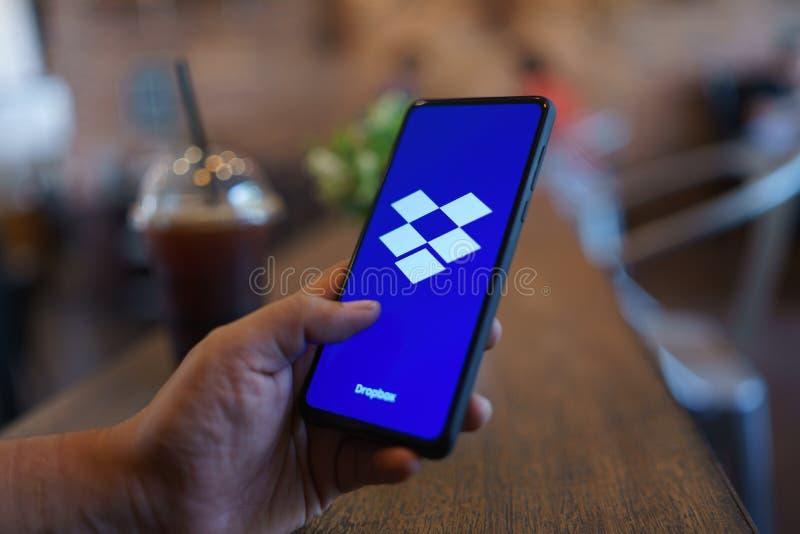 E 24,2019: Человек держа смешивание 3 Xiaomi Mi с Dropbox на экране Dropbox обслуживание которое дает вам доступ стоковое изображение