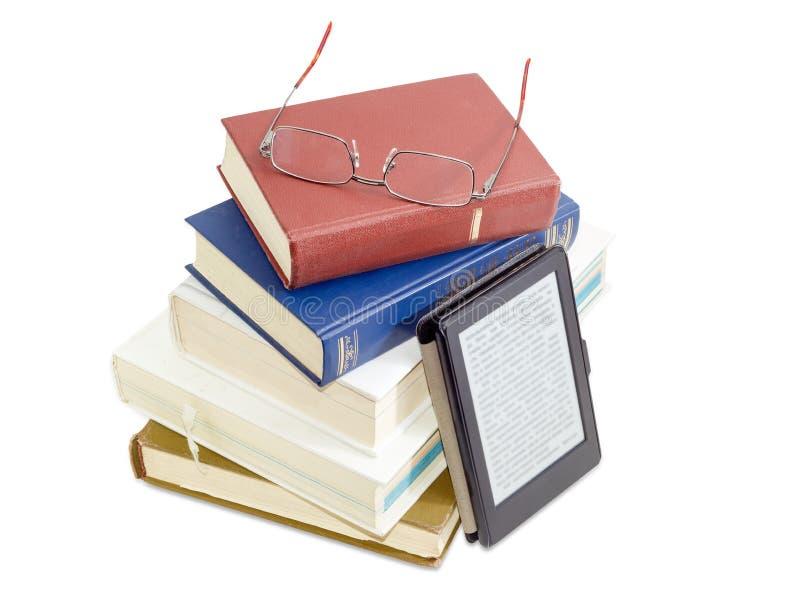 E-читатель и стог обычных бумажных книг с eyeglasses стоковые изображения rf