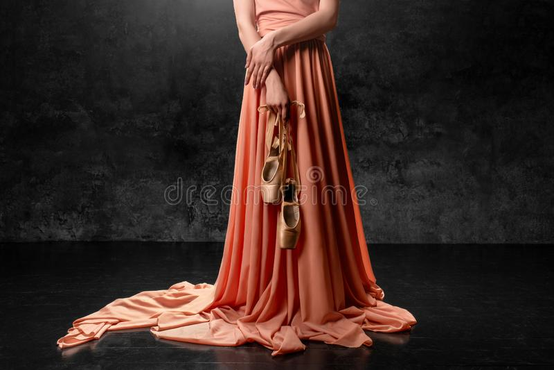 E 一个年轻优美的舞蹈家身分对在一件长的桃子礼服穿戴的黑墙壁,保持向下使pointe鞋子的手 库存照片