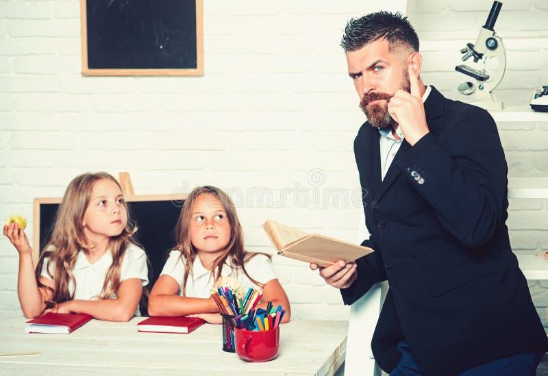 E 上课时间姐妹和父亲在图书馆里 老师人读了故事给吃苹果的女孩 图库摄影