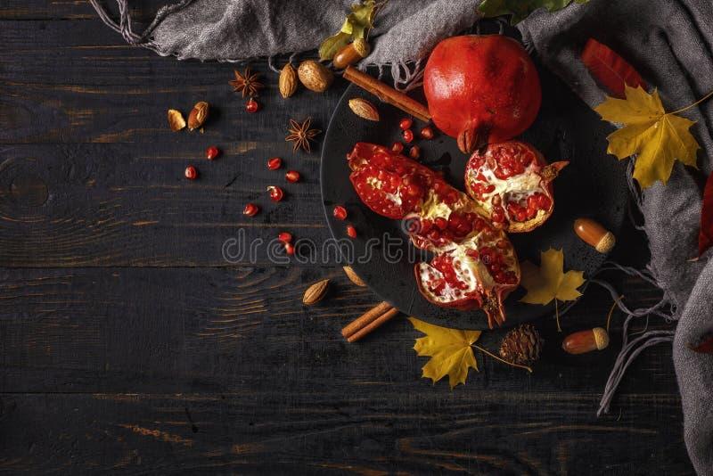E 与坚果、香料和干燥叶子的石榴在一张黑暗的木桌上 r r 图库摄影