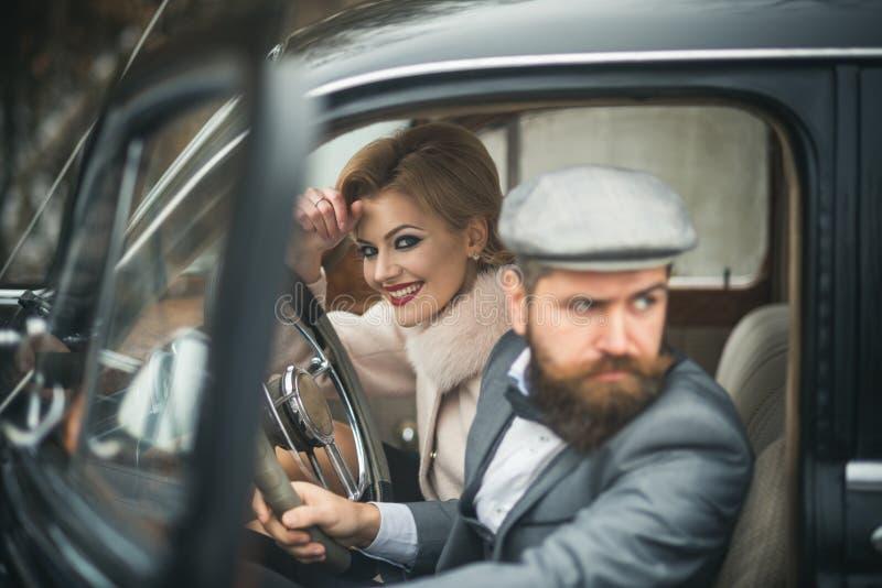 E 与有胡子的司机和豪华女孩的伴游概念减速火箭的汽车的 图库摄影