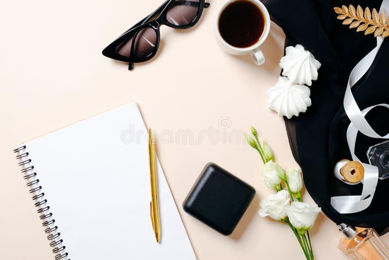E 与白纸笔记本、咖啡杯、圆环箱子、蛋白软糖和玫瑰花的女性工作区 免版税库存照片