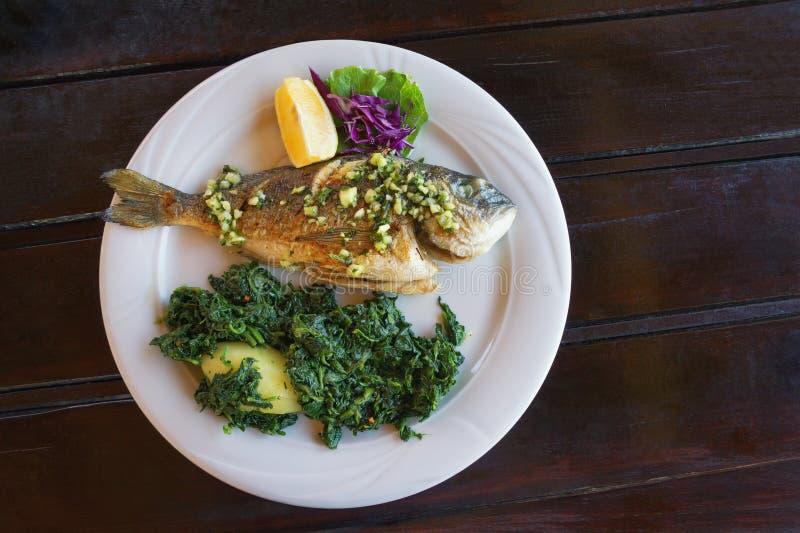 E 与绿叶蔬菜的烤鱼海鲷在白色板材 r 库存图片