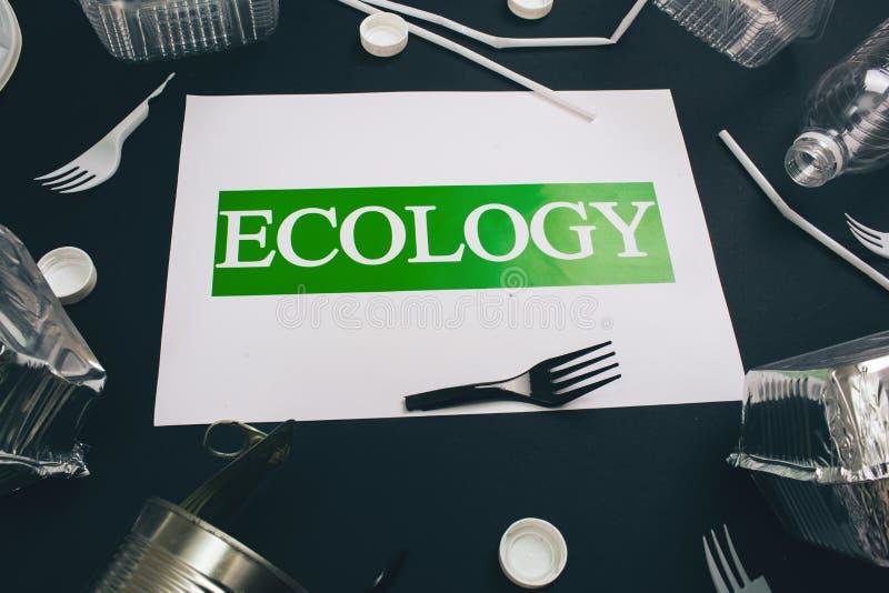E 与词生态的纸在单一用处金属罐头,箔容器,秸杆,残破的叉子附近 免版税库存图片