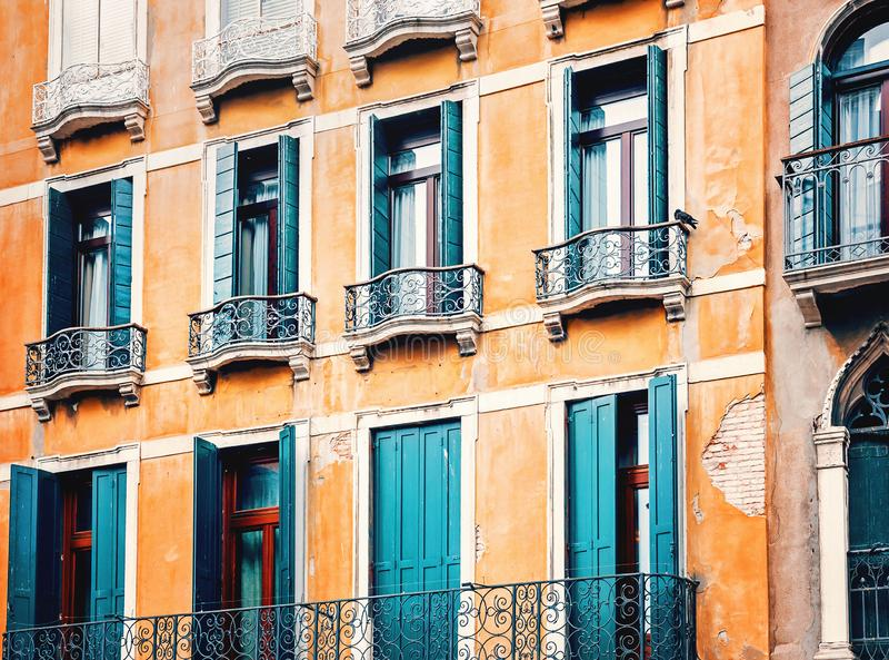 E 与阳台和小野鸭木快门的传统威尼斯式历史的橙色大厦 免版税库存照片