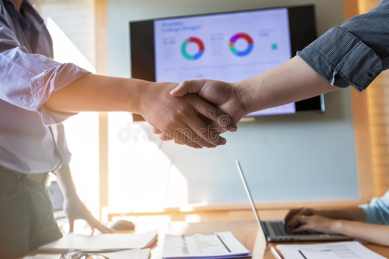 E 两握手的确信的商人在一次会议期间在办公室, 库存照片