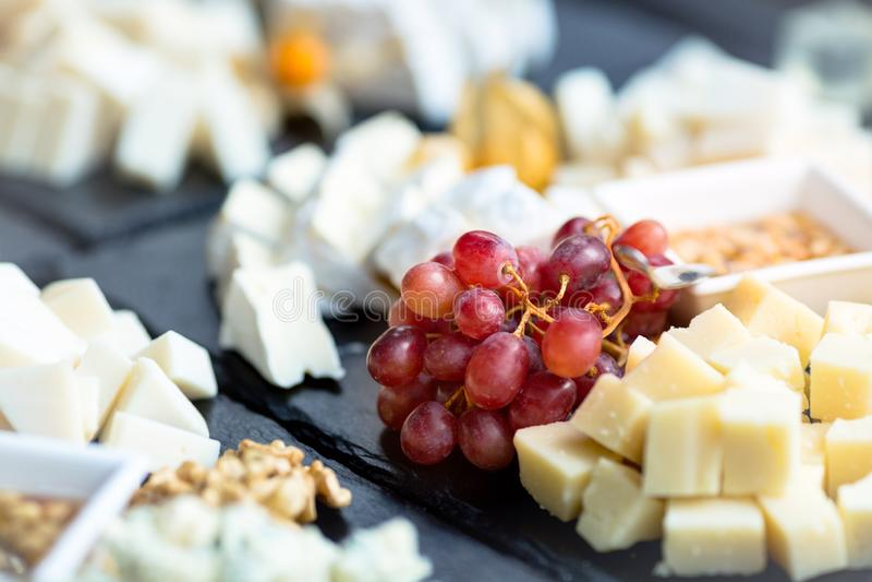 E 乳酪的各种各样的类型用在黑板岩石头的葡萄 关闭与选择聚焦的图象 免版税库存图片