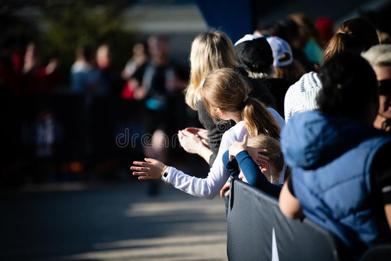 E 人群在家庭舒展观看赛跑者完成 库存照片