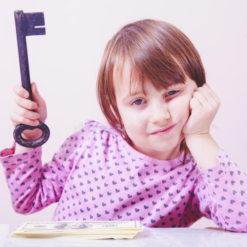 E 作为财富和安全的标志的逗人喜爱的女孩藏品钥匙 库存照片