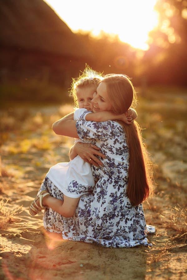 E E 使用与她的小小女儿女孩的母亲在阳光夏日 库存照片