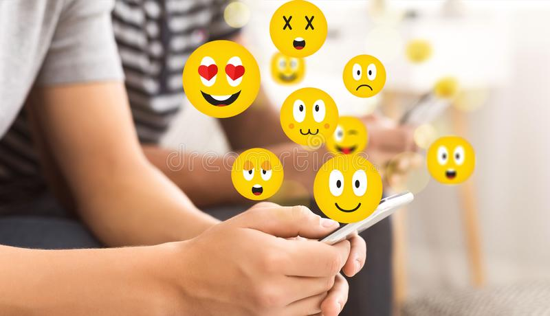 E 使用智能手机的青少年的人送emojis 库存照片