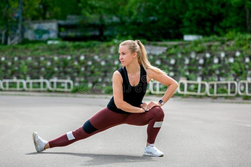 E 做准备在训练做的锻炼前的年轻女人舒展她的肌肉和联接 在的锻炼 免版税图库摄影
