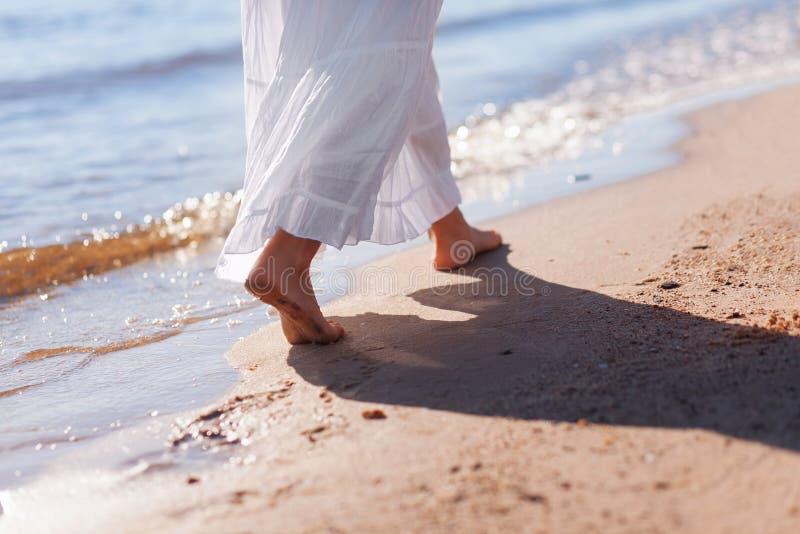 E 关闭走由海滩的女性腿 脚在水夏天 r 波浪和沙子 库存照片