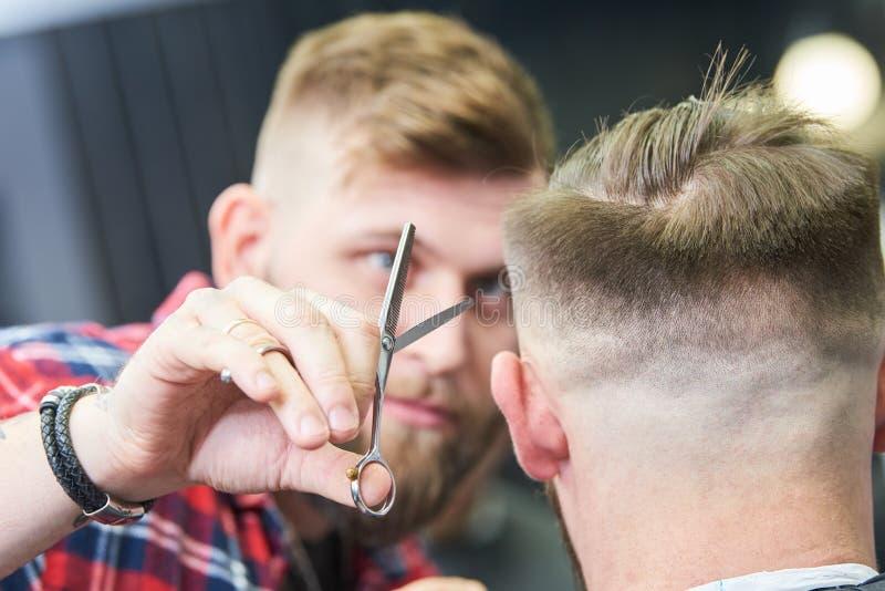 E 剪客户的头发的美发师 免版税库存照片