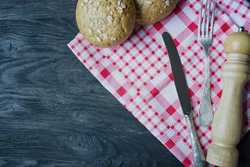 E 叉子,食物刀子,方格的餐巾,与向日葵种子,木胡椒振动器的小圆面包 ?? 库存照片