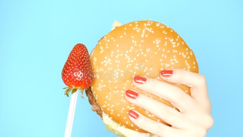 E 反对汉堡包的草莓在明亮的蓝色背景 女性手与 免版税库存照片