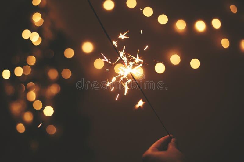E 发光的闪烁发光物在手中在金黄圣诞树光背景,庆祝在黑暗的欢乐室 ?? 库存照片