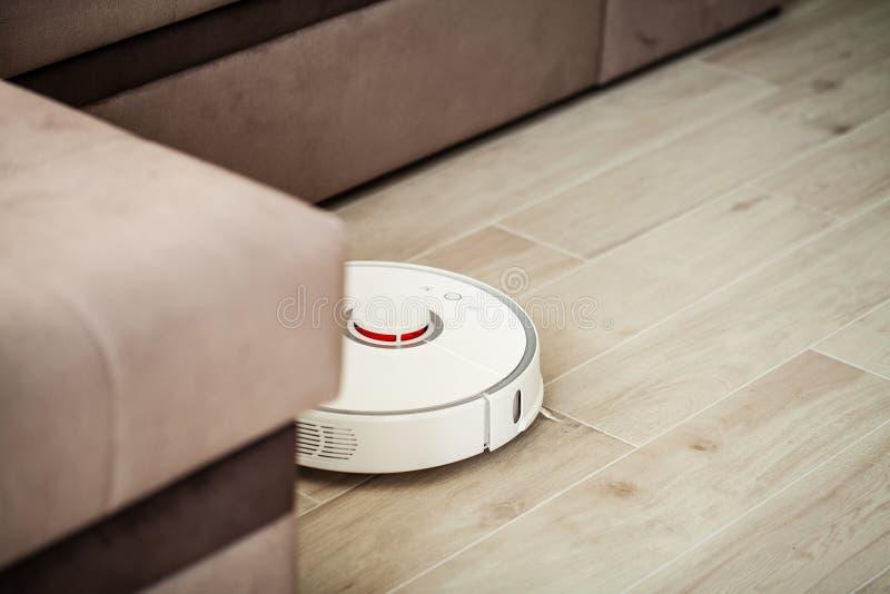 E 吸尘器机器人在木地板上运行在客厅 免版税库存照片