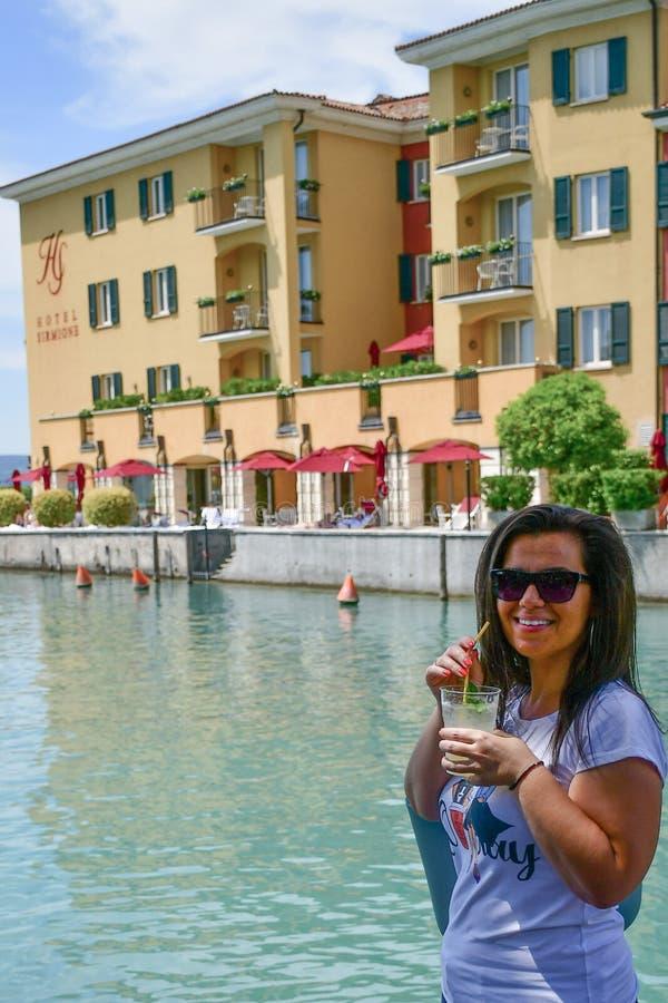 E 喝在Garda湖的微笑的妇女冰冷的柠檬水 免版税库存图片